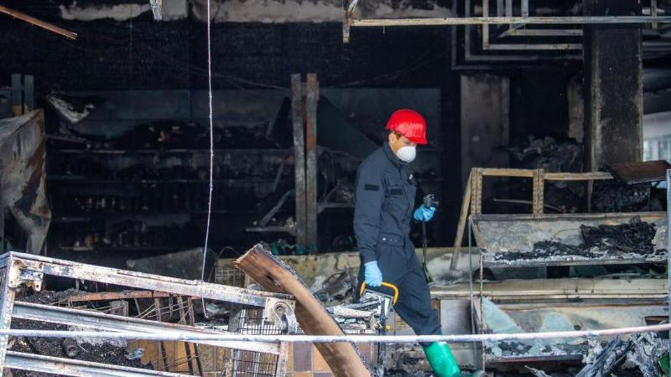 Ein Brandermittler der Polizei sucht drei Tage nach dem Brand eines türkischen Geschäfts nachSpuren. Foto: Lino Mirgeler/dpa/Archiv