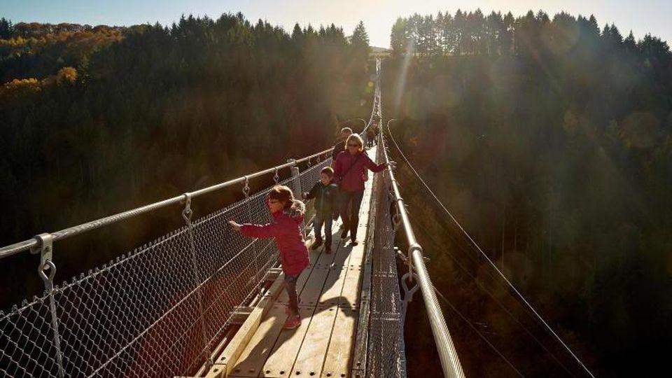 Besucher gehen über die Geierlay-Brücke zwischen den Hunsrückgemeinden Mörsdorf und Sosberg. Foto: Thomas Frey/dpa/Archivbild