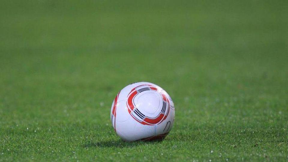 Ein Fussball liegt auf dem Rasen. Foto: picture alliance / dpa / Archivbild