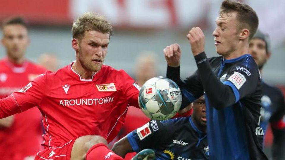 Paderborns Sebastian Schonlau (r) im Kampf um den Ball mit Berlins Sebastian Andersson (l). Foto: Friso Gentsch/dpa