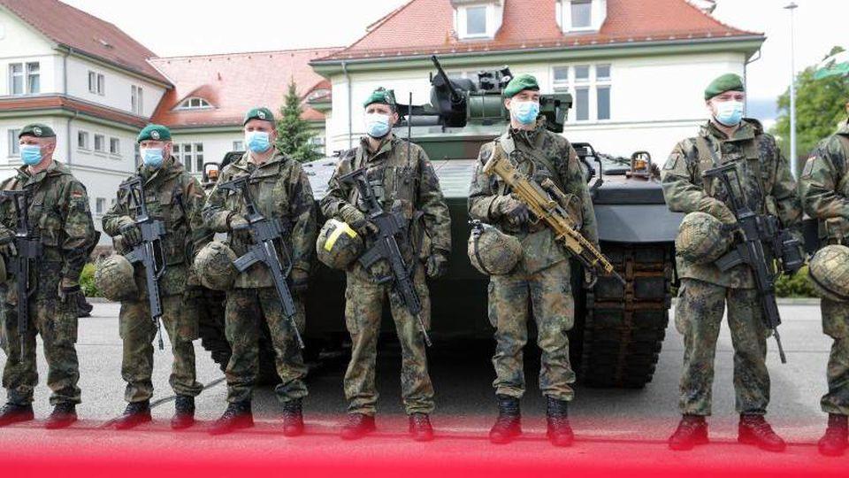 """Soldaten der Panzergrenadierbrigade 37 vor einem Schützenpanzer """"Marder"""". Foto: Jan Woitas/dpa-Zentralbild/dpa"""