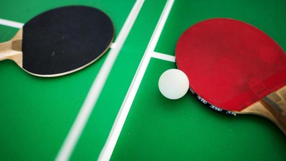 Auf einer grünen Tischtennisplatte in Berlin liegen ein roter und ein schwarzer Tischtennisschläger und ein Tischtennisball. Foto: Arno Burgi/dpa-Zentralbild/dpa/Archivbild