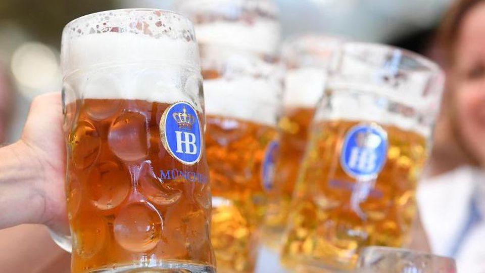Feiernde stoßen mit ihren Bierkrügen an. Foto: Tobias Hase/dpa-tmn/Symbolbild