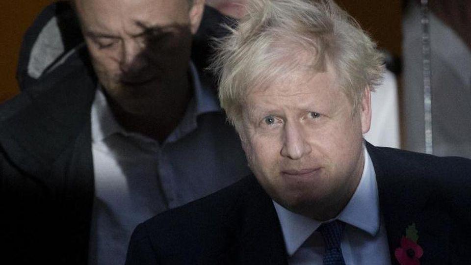 Premier Boris Johnson (l) und sein wichtigster Berater Dominic Cummings. Ein weiterer Mitarbeiter musste nach rassistischen Äußerungen gehen. Foto: Matt Dunham/AP/dpa