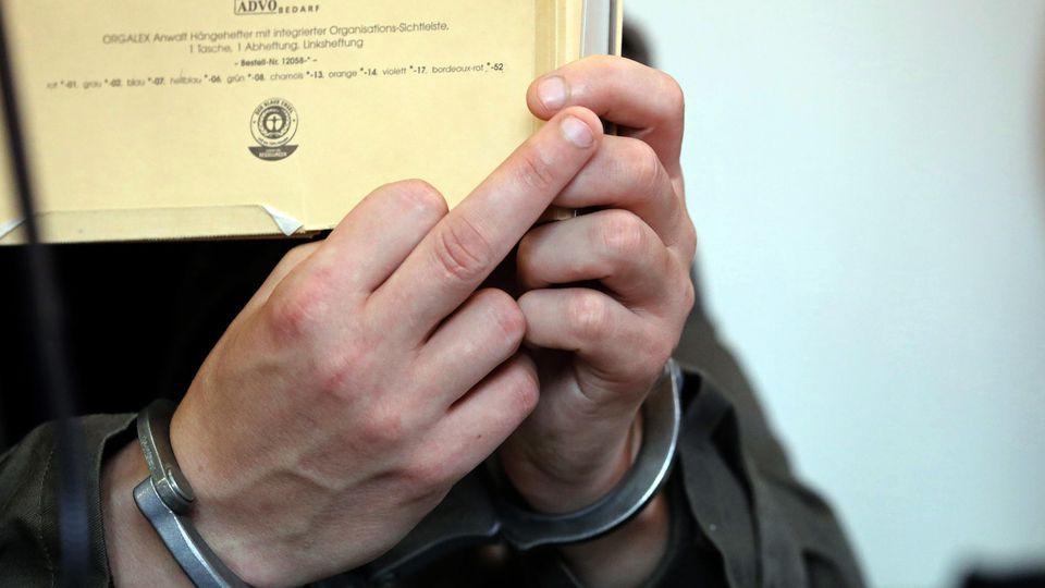 Mecklenburg-Vorpommern, Neubrandenburg: Vor Beginn des Prozesses wegen Mordes durch Unterlassen und Misshandlung von Schutzbefohlenen in sieben Fällen hält sich der angeklagte Stiefvater einen Aktendeckel vor das Gesicht