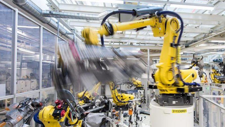 In der deutschen Industrie scheint es wieder aufwärts zu gehen:Industrieroboter schweißen in einer Volkswagen Autofabrik Teile an. Foto: picture alliance / Silas Stein/dpa