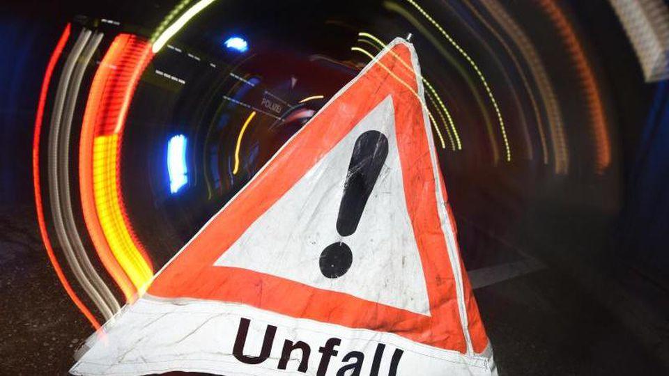 """Ein Warndreieck mit dem Schriftzug """"Unfall"""" steht vor einem Blaulicht auf der Straße. Foto: Patrick Seeger/dpa/Symbolbild"""