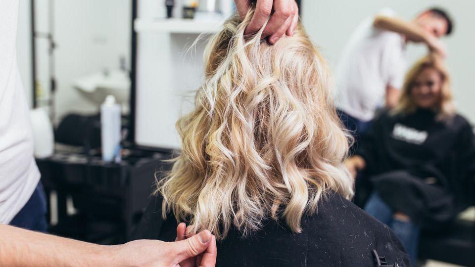 Friseur stylt Haare von Frau.