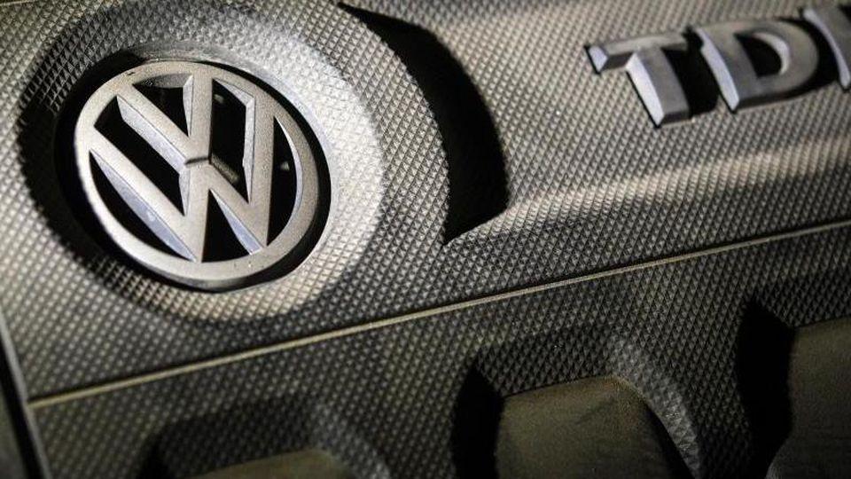 Das Logo von Volkswagen auf einer Motorabdeckung eines VW Golf 2,0 TDI. Foto: Patrick Pleul/Archivbild