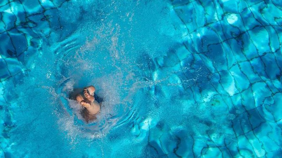 Eine Frau taucht ins Becken ein. Foto: Sebastian Gollnow/dpa/Illustration