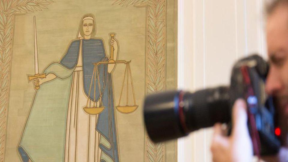 Ein Fotograf vor dem Bild der Justitia. Foto: Friso Gentsch/Archiv