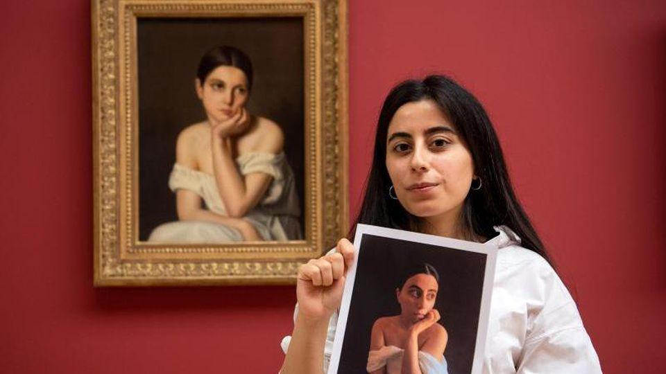 """Selvinaz Özdemir mit einem Foto ihrer Interpretation von """"Junges Mädchen (Melancholie)"""" von Théodore Chassériau. Foto: Sina Schuldt/dpa"""