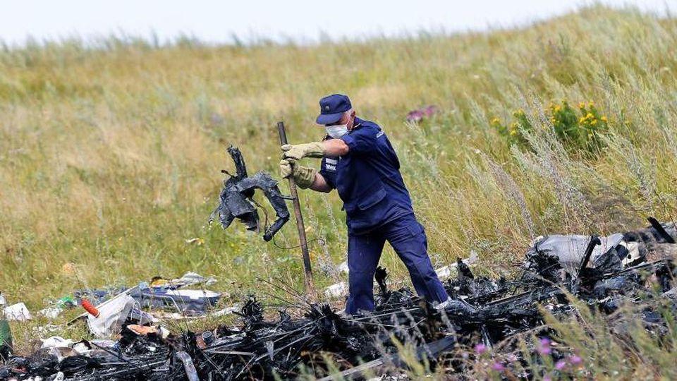 Ein ukrainischer Arbeiter untersucht im Juli 2014 an der Absturzstelle von MH17 Wrackteile der Maschine. Foto: Robert Ghement/epa