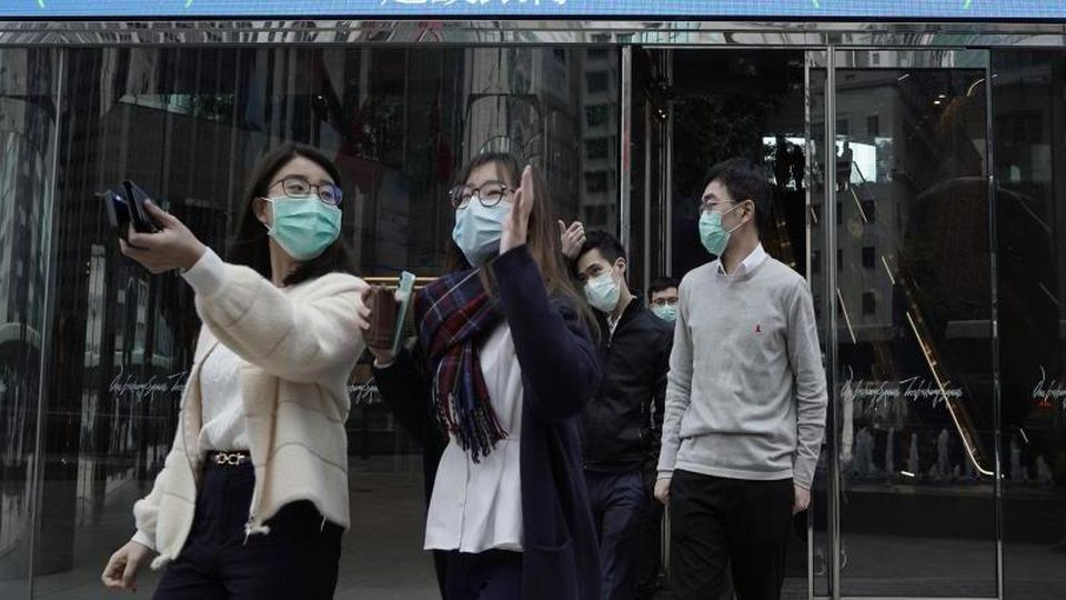 Personen mit Mundschutz gehen über eine Straße in China. Foto: Kin Cheung/AP/dpa/Archivbild