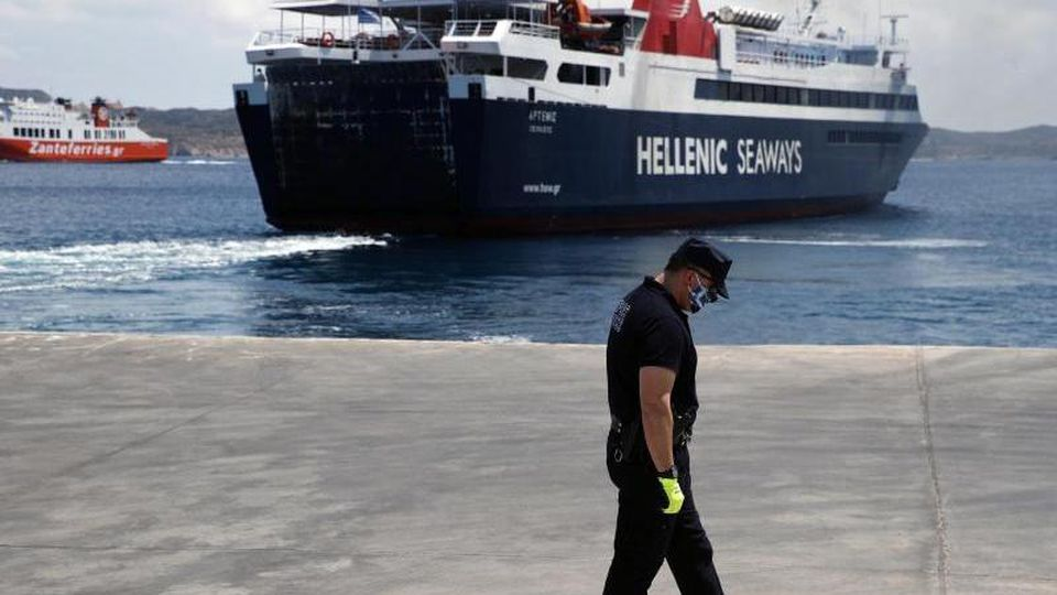 Ein Offizier der Küstenwache auf dem Dock vor einer Fähre zur Ägäisinsel Milos. Foto: Thanassis Stavrakis/AP/dpa