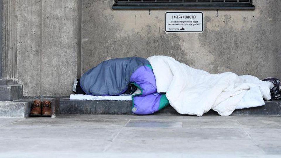 Ein Obdachloser liegt unter Decken am Straßenrand. Foto: Tobias Hase/dpa/Archivbild