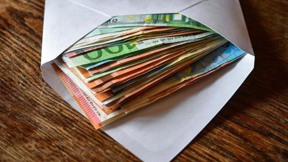 Mehrere Eurobanknoten liegen in einem Briefumschlag. Foto: Patrick Pleul/Archiv