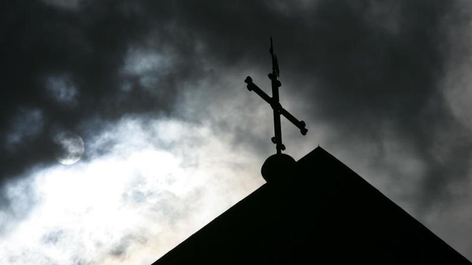 Vor wolkenverhangenem Himmel ist eine Kirchturmspitze mit Kreuz zu sehen. Foto: Friso Gentsch/dpa/Symbolbild