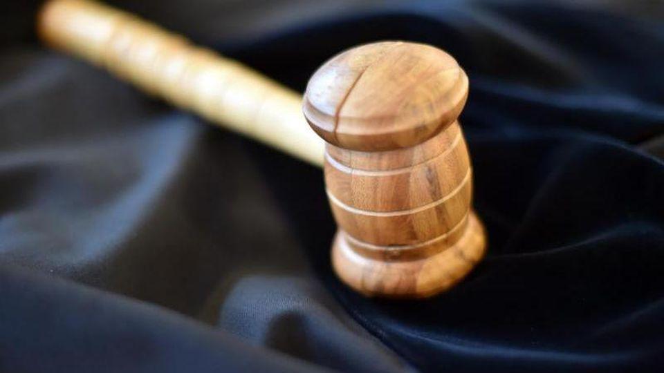Auf einem Tisch in einem Gerichtssaal liegt ein Richterhammer aus Holz, darunter eine Richterrobe. Foto: picture alliance / dpa/Symbolbild