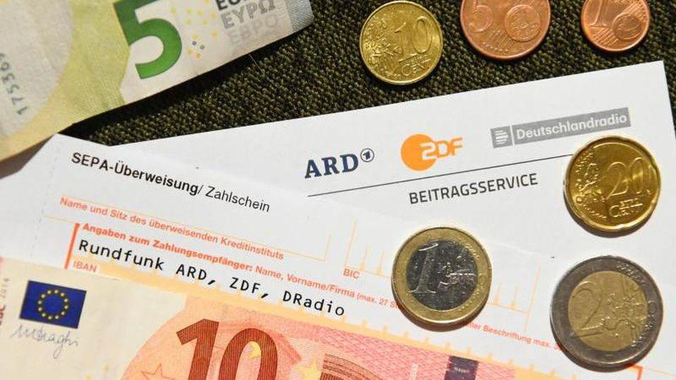Auf einem Tisch liegt ein Anschreiben und Überweisungsträger für die Rundfunkgebühren, sowie der Betrag von 18 Euro und 36 Cent. Foto: Nicolas Armer/dpa/Archivbild