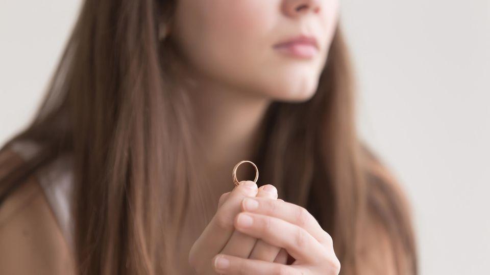 Frau hält Ehering in der Hand.