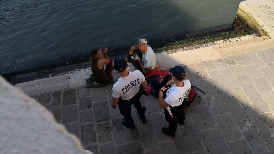 HANDOUT - 19.07.2019, Italien, Venedig: Zwei deutsche Touristen werden von zwei Polizisten an der Treppe der Rialto-Brücke angesprochen, da sie sich mit einem kleinen Kaffeekocher Kaffee auf dem Gehweg zubereitet haben. (zu dpa «Deutsche Touristen ko