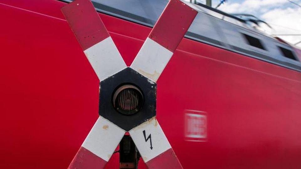 Ein Personenzug der Deutschen Bahn (DB) fährt hinter einem blinkenden Andreaskreuz an einem Bahnübergang vorbei. Foto: Jens Büttner/Archiv