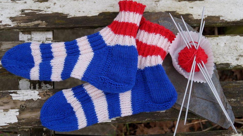 Selbstgestrickte blau-weiß-rot gekringelte Socken mit Hebemaschen.
