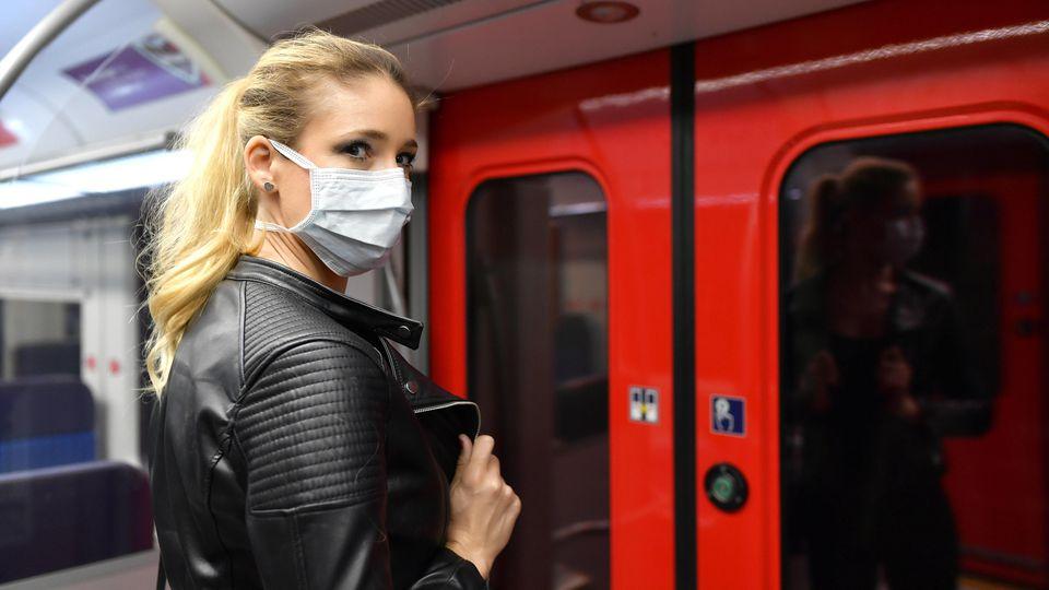 Frau steht mit Mundschutzmaske in der S-Bahn.