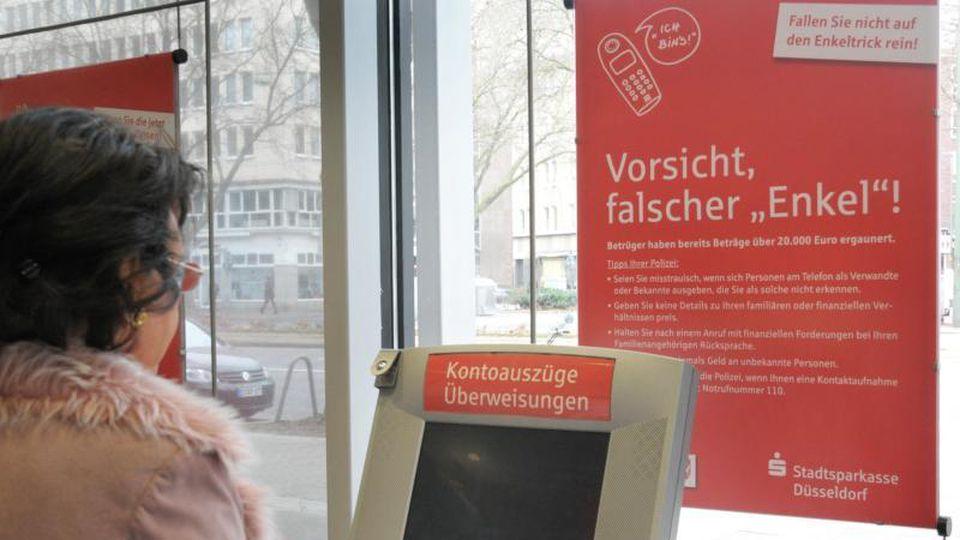 """Eine Frau bedient einen Geldautomaten, im Hintergrund warnt ein Plakat vor """"falschen Enkeln"""". Foto: Horst Ossinger/Archiv"""