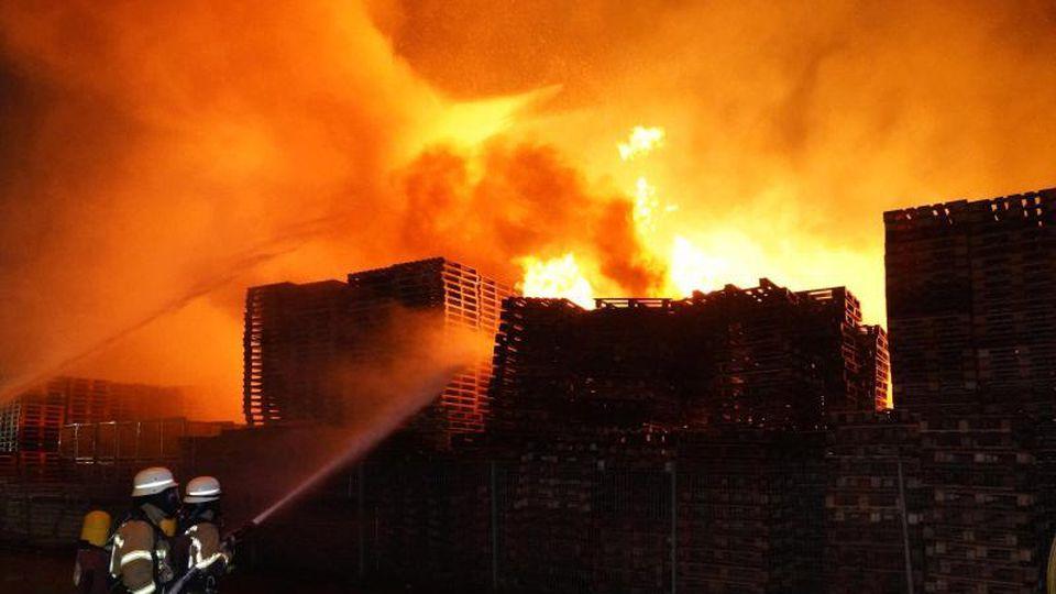 Feuerwehrleute versuchen Stapel von brennenden Holzpaletten zu löschen. Foto: Andreas Rosar/dpa