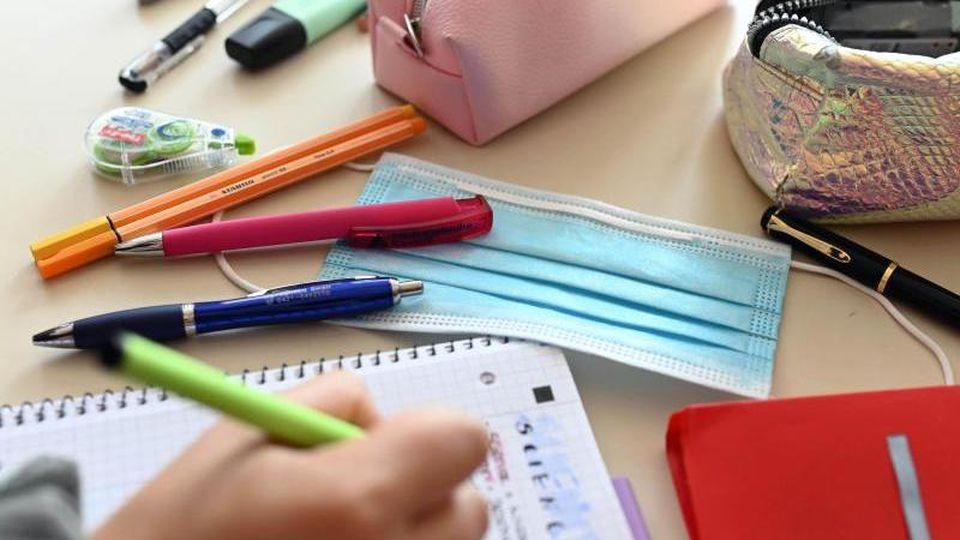 Während einer Unterrichtsstunde einer zehnten Klasse liegt ein Mund-Nasen-Schutz auf dem Tisch einer Schülerin. Foto: Uli Deck/dpa/Archivbild