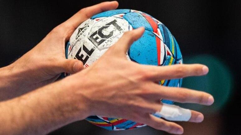 Ein Handballer hält den Spielball in seinen Händen. Foto: Robert Michael/dpa/Symbolbild