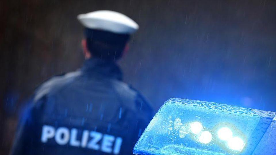 Ein Polizist steht vor einem Streifenwagen. Foto: Karl-Josef Hildenbrand/dpa/Symbolbild