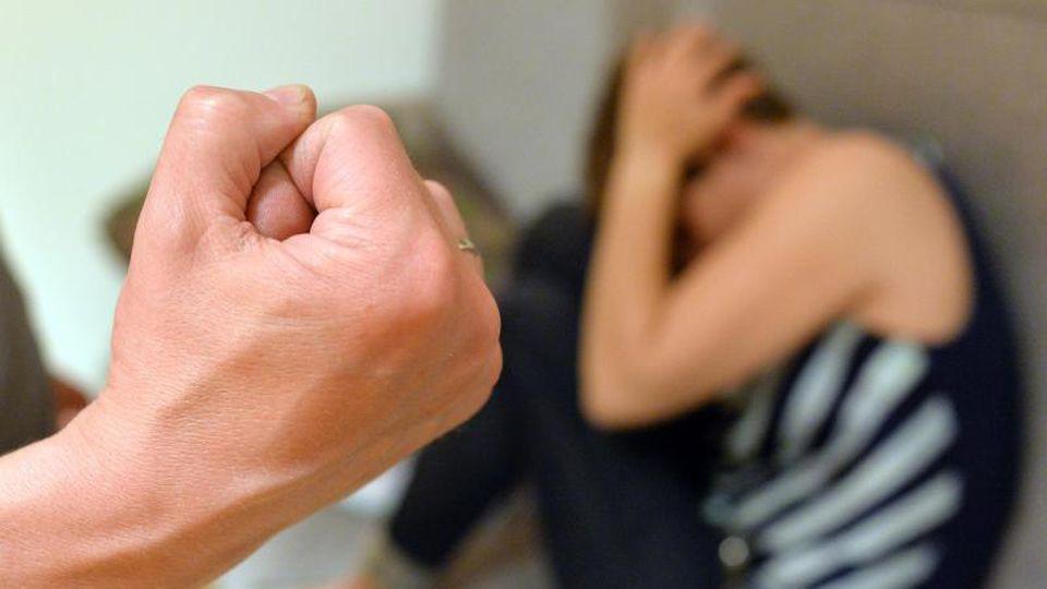 Eine Frau versucht, sich vor der Gewalt eines Mannes zu schützen (gestellte Szene). Foto: Maurizio Gambarini/dpa/Illustration