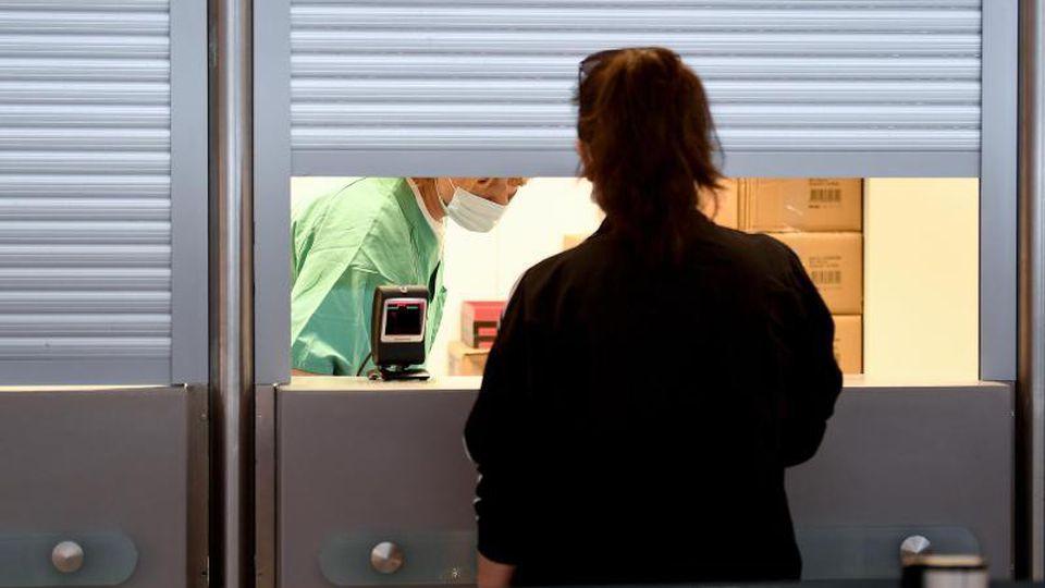 Eine Frau steht am Flughafen Tegel am Corona-Teststand. Foto: Britta Pedersen/dpa-Zentralbild/dpa
