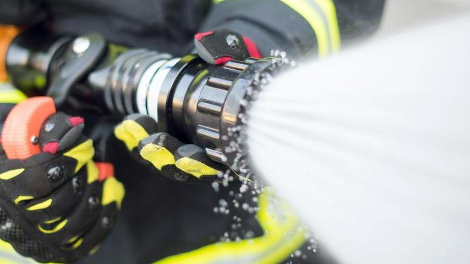Ein Feuerwehrmann löscht. Foto: Daniel Bockwoldt/dpa/Archiv/Illustration