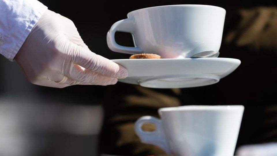 Eine Servierkraft bringt Gästen eines Cafés mit Gummihandschuhen Kaffee. Foto: Robert Michael/dpa-Zentralbild/dpa/Archiv/Symbolbild