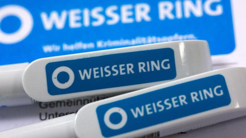 Kugelschreiber des Verbands Weißer Ring liegen auf einem Informationsschreiben. Foto: Jens Büttner/dpa-Zentralbild/dpa/Symbolbild