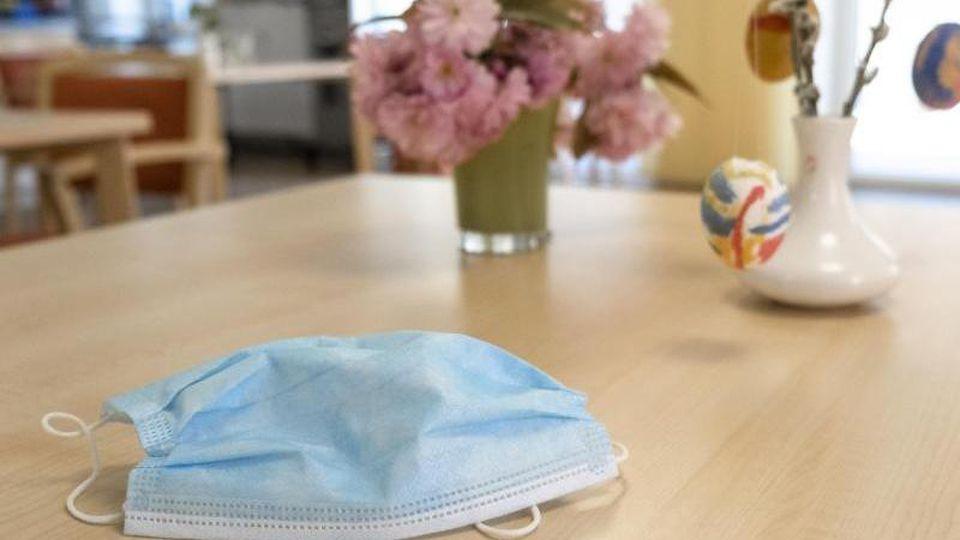 Ein Mundschutz liegt auf einem Tisch einer Pflege- und Senioreneinrichtung. Foto: Frank Molter/dpa/Symbolbild