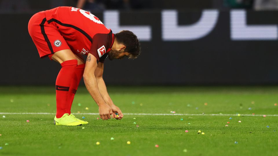 Goncalo Paciencia of Eintracht Frankfurt removes small objects from the ground prior to the Bundesliga match between VfL Wolfsburg and Eintracht Frankfurt at Volkswagen Arena on April 22, 2019 in Wolfsburg, Germany. (P