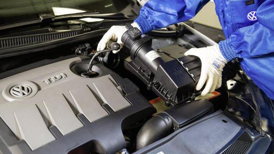 Ein VW-Mitarbeiter baut einen um einen Strömungsgleichrichter erweiterten Luftfilter in einen Dieselmotor der Typreihe EA 189 ein. Foto: Volkswagen