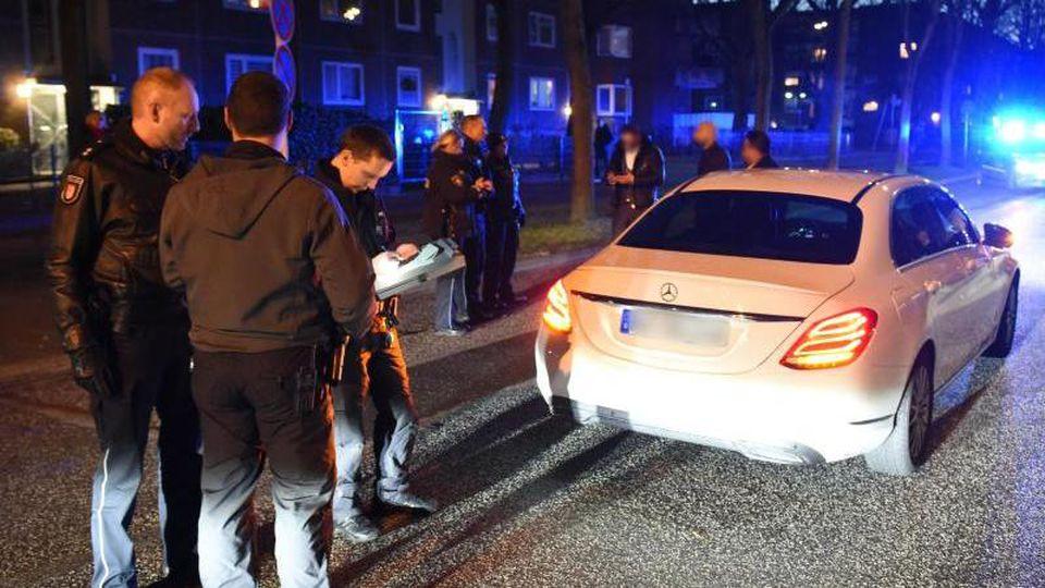 Polizisten kontrollieren ein Auto des gestoppten Hochzeitskorsos. Foto: Daniel Bockwoldt