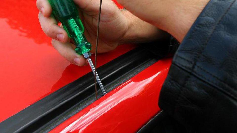 Eine Autotür wird mit Hilfe eines Schraubenziehers geöffnet. Foto: Heiko Wolfraum/dpa/Archivbild