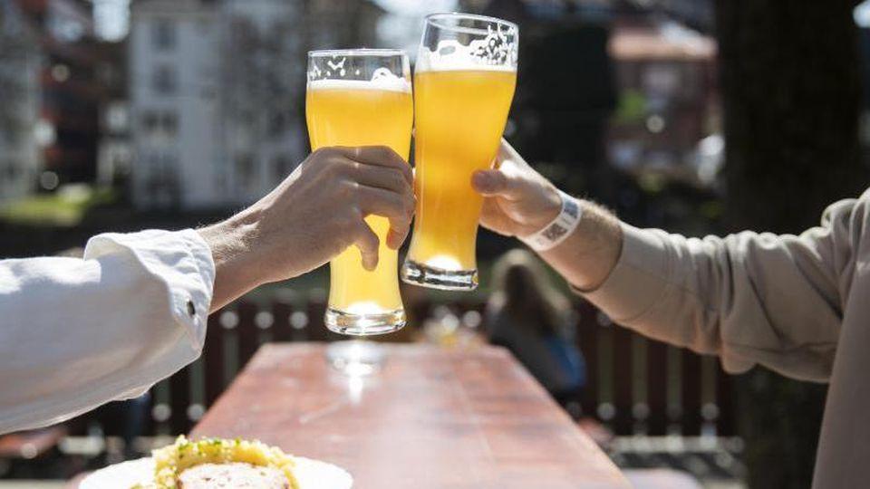 Gäste sitzen bei gutem Wetter in einem Biergarten und stoßen mit einem Bier an. Foto: Tom Weller/dpa/Archivbild