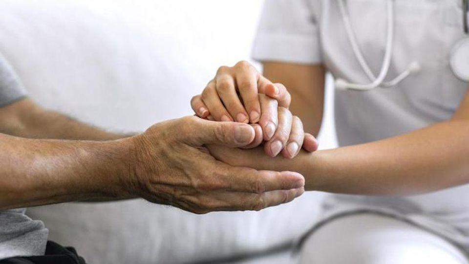 Eine Pflegerin hält die Hand eines Patienten. Foto: CLARK/obs/Archivbild
