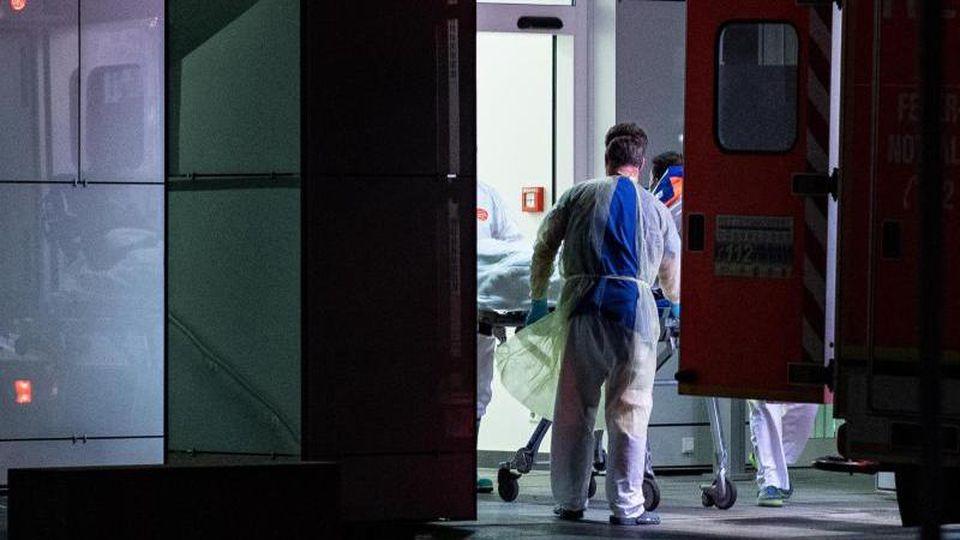 Mitarbeiter des Universitätsklinikums in Düsseldorf nehmen den infizierten Patienten in Empfang. Foto: Guido Kirchner