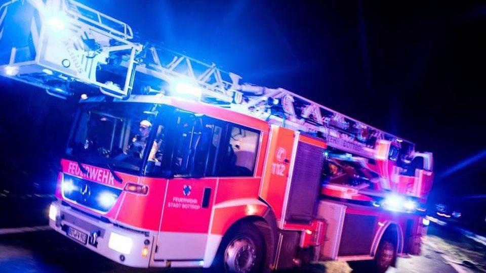 Ein Drehleiterwagen der Feuerwehr fährt mit Blaulicht an einer Unfallstelle vorbei. Foto: Marcel Kusch/dpa/Illustration