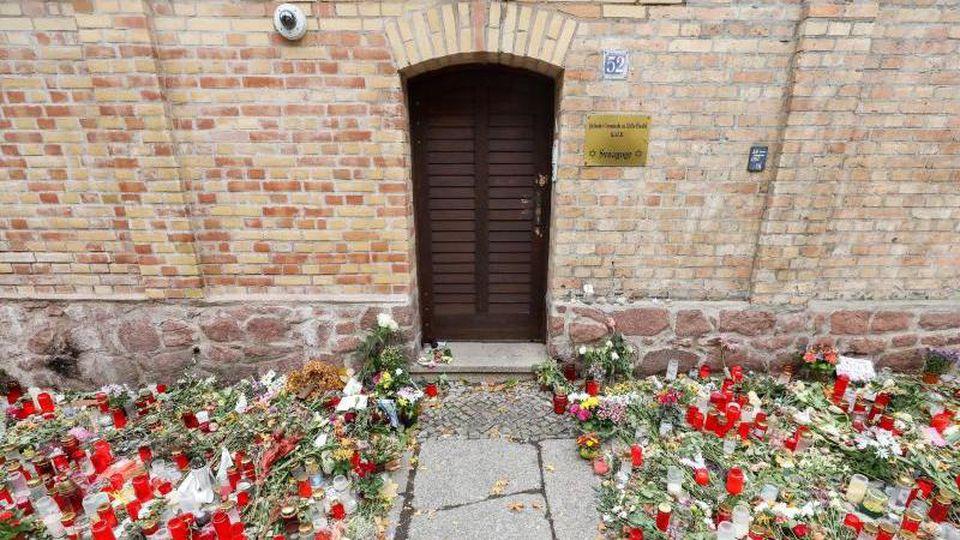 Blumen und Kerzen stehen vor derTür der Synagoge. Foto: Jan Woitas/zb/dpa/Symbolbild