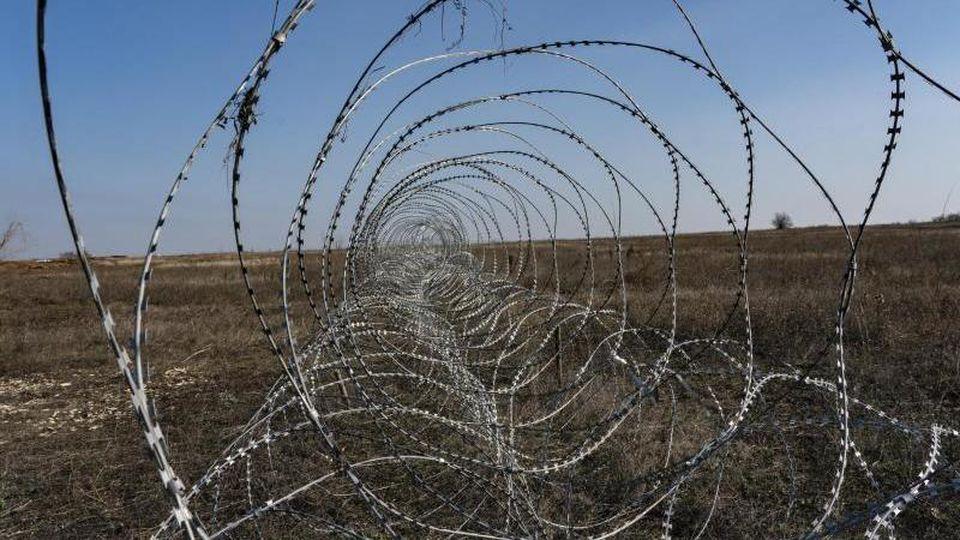 Stacheldraht durchzieht die umkämpften Gebiete der Ostukraine. Foto: Evgeniy Maloletka/AP/dpa